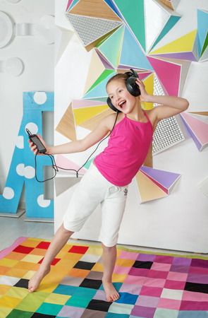 Child girl dances and sings. Listen to music. The concept of music and childhood.