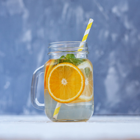 Refreshing detox water with lemon, orange and mint. Glass jar and tubule. Square. The concept is summer, diet, vegetarian, fitness, healthy eating and lifestyle.