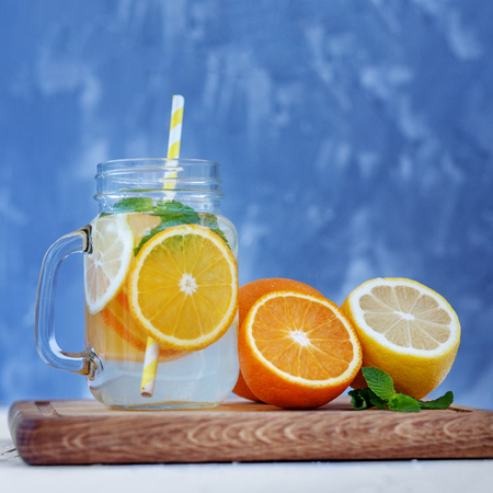 Refreshing cocktail with lemon, orange and mint. Glass jar and tubule. Square. The concept is summer, diet, vegetarian, fitness, healthy eating and lifestyle.