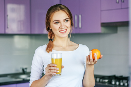 Young woman drinking orange juice in the kitchen. The concept is healthy food, diet, vegetarianism, weight loss. Фото со стока
