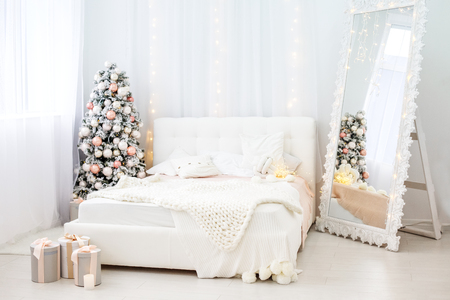 Room with bed and mirror and fir tree. Concept Happy Christmas, New Year, holiday, winter, greetings.