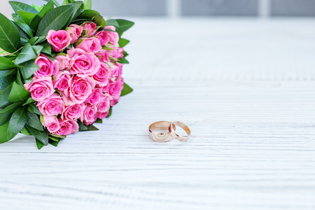 Bouquet of pink roses. Wedding ring. Background. Copy space. The concept of a wedding, party, love and family.