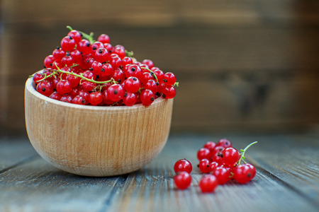 Useful red currants in a wooden bowl. The concept is healthy food, vitamins, diet and vegetarianism.