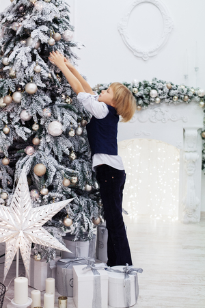 Little boy decorating the Christmas tree. The concept of Christmas