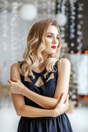 Young beautiful woman in a black dress for Christmas. Concept of Happy Christmas and New Year, winter, party.