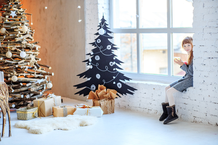 A beautiful child sits on the window sill and drinks tea. Concept Happy Christmas, New Year, holiday, winter, childhood.