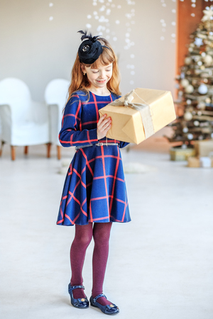 A beautiful kid got a gift box and admired.  Concept Happy Christmas, New Year, holiday, winter, childhood. Imagens