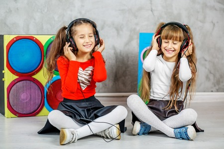 Two girls are listening to music on headphones. Concept music, radio, dance, life stroke, rest.