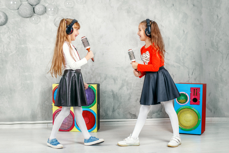 Funny little girls sing and listen to music in headphones. The concept is childhood, lifestyle, dance, music.