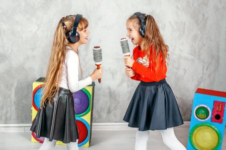 Niños graciosos cantando y escuchando música con auriculares. El concepto es infancia, estilo de vida, danza, música. Foto de archivo