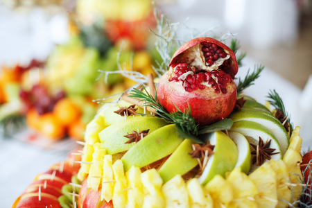 Fruit mix of pomegranate, apple, pineapple, orange. The concept of healthy and useful food. Stock Photo