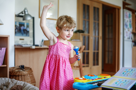 The little child dances and sings in the microphone. Conception childhood, upbringing, music.