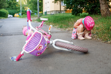 The child fell from a bicycle and cries. The concept of childhood and lifestyle.
