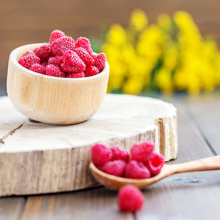 Juicy raspberries in a wooden bowl. Place for text. The concept is healthy food, diet, vegetarianism, vitamins.