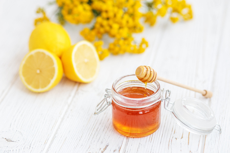 Useful honey and lemon. Honey dipper. The concept of healthy food, vegetarianism, autumn, colds,  treatment, cure, therapy, medication. Imagens