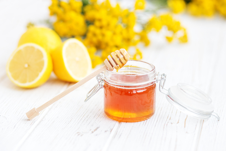 Handige en heerlijke honing en citroen. Honingdipper. Het concept van gezonde voeding, vegetarisme, herfst, verkoudheid, behandeling, genezing, therapie, medicatie.