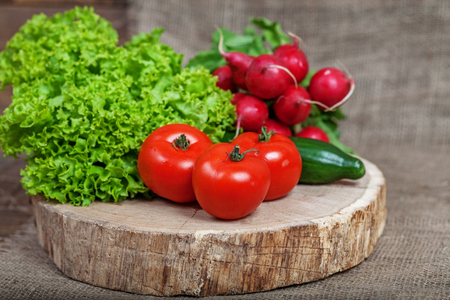 Tomatoes, cucumbers, radishes and lettuce. Vegetables..The concept of healthy eating and vegetarianism. Stock Photo