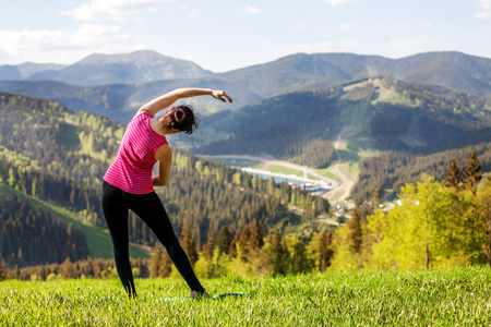 The young girl practices yoga on the mountain. The concept of a healthy lifestyle, travel and yoga.