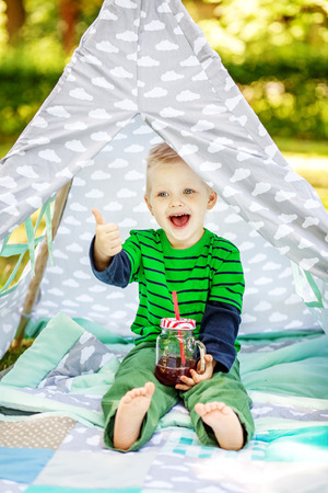 Funny little boy with juice. 2-3 years. Child. The concept of lifestyle picnic and childhood. Stock Photo