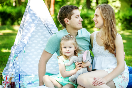 Mother, father and little daughter at a picnic in the park. The concept of family, lifestyle and children.