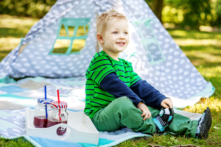 Funny funny little boy sitting in the park. 2-3 years. The concept of lifestyle picnic and childhood. Stock Photo