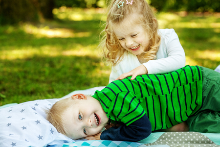 Little brother and sister hugging and laughing. The concept of lifestyle picnic and childhood.