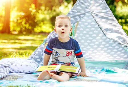 Surprised child with a book in the park. Boy preschool. The concept of childhood, learning and lifestyle.