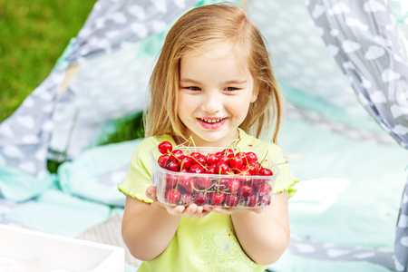 The little baby has a cranberry package. The concept is healthy food, childhood and lifestyle.