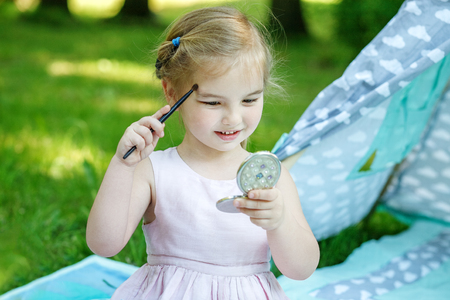 A little beautiful baby with a mirror. The girl is drawn with cosmetics. The concept is childhood, lifestyle, beauty, fashion, summer. Stock Photo