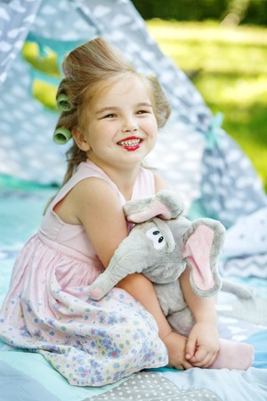 Little child with red lipstick and swaddlers. The girl hugs her elephant. The concept is childhood, lifestyle, beauty, fashion, summer. Stock Photo