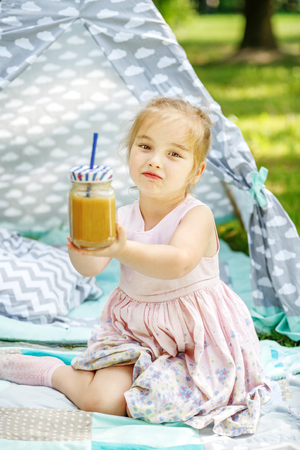 The kid drinks a smoothie in the park. The concept is healthy food, childhood and lifestyle.