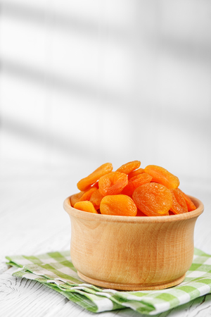A useful dried apricot in a wooden bowl. The concept is healthy food, vegetarianism, diet, vitamins.