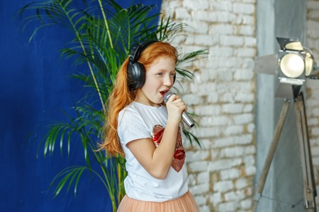 A red-haired little girl sings a song in a microphone. The concept is childhood, lifestyle, music, singing, listening, hobbies.