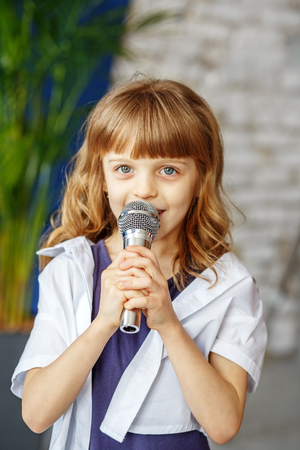 A little beautiful kid sings a song in a microphone. The concept is childhood, lifestyle, music, singing, listening, hobbies.