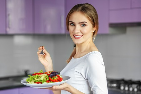 Smiling young woman with a plate of vegetable salad. The concept is healthy food, diet, vegetarianism, weight loss.