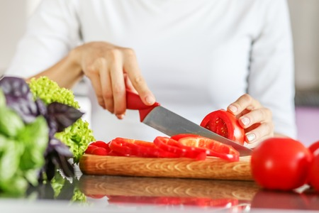 A young man slicing tomatoes with a sharp knife. The concept is healthy food, diet, vegetarianism, weight loss.