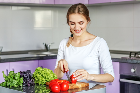 Young happy woman is preparing a delicious lunch in the kitchen. Vegetarian. The concept is healthy food, diet, vegetarianism, weight loss.