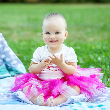 Little baby sitting and laughing in a pink skirt. Concept of chi Stock Photo