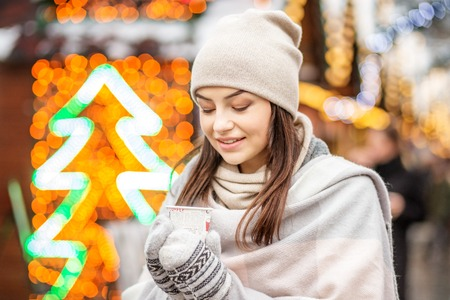 A young woman drinks coffee in the street in winter. Concept Lif
