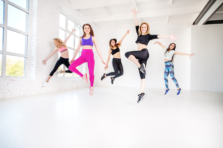 Young women dancing in the gym. Jump. The concept of sport, dance and a healthy lifestyle.
