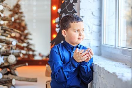 A little boy drinks tea and looks in the window.