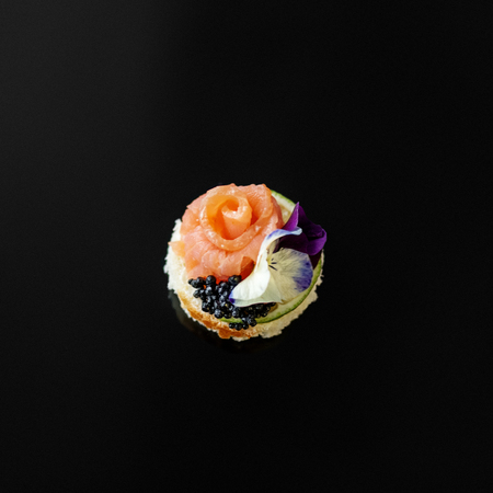 Delicious appetizer with fish and edible flowers. Concept for food, restaurant, menu, catering.