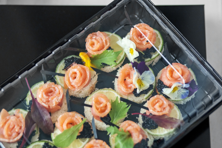Delicious appetizer with fish and edible flowers in lunch box. Concept for food, restaurant, menu, catering.
