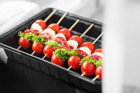 Delicious gourmet snacks with cherry, meat and mozzarella in lunch box. Concept for food, catering, restaurant, party.