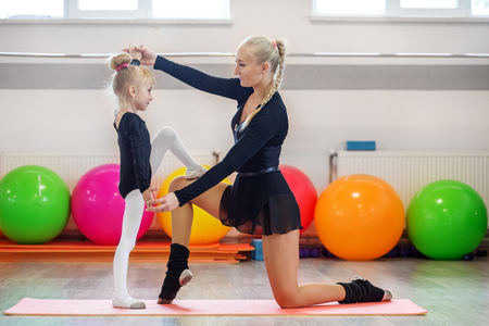 Athletic trainer teaches child aerobics. The concept of sports, education, hobbies, training and dance 스톡 콘텐츠
