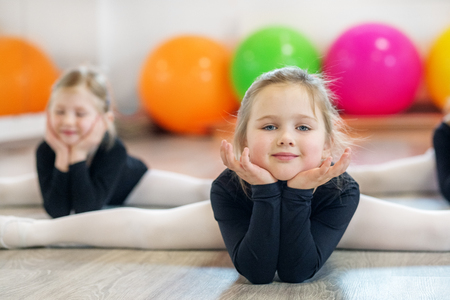 Little girl doing stretching in training. The concept of sport, education, hobbies, training.