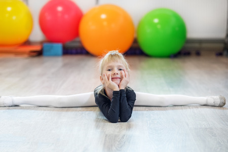 Happy little girl is sitting on the splits in the gym. The concept of sports, education, hobbies, training and dance