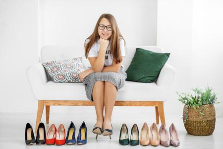 Jeune fille élégante et beaucoup de chaussures. Concept mode, shopping, vêtements, style de vie, centre commercial. Banque d'images