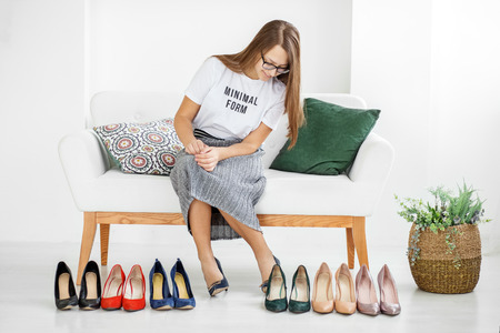 Young stylish girl chooses his shoes. Concept fashion, shopping, clothing, lifestyle.