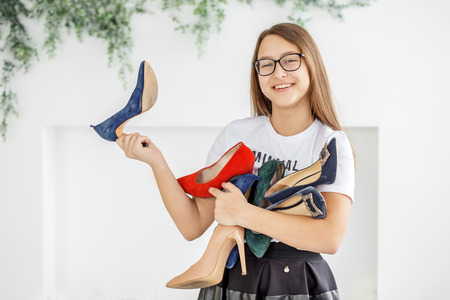 A smiling girl buys a lot of shoes. Sale. Concept fashion, shopping, clothing, lifestyle, shopping center.